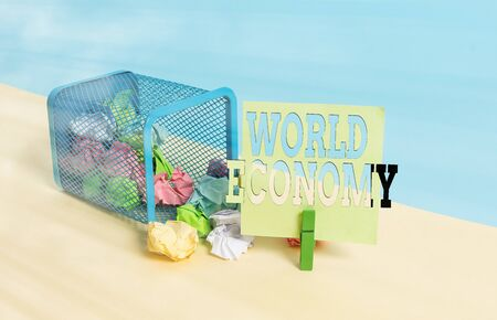 Word writing text World Economy. Business photo showcasing Global Worldwide International markets trade money exchange Trash bin crumpled paper clothespin empty reminder office supplies tipped