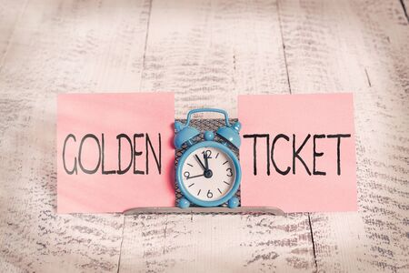 Writing note showing Golden Ticket. Business concept for Rain Check Access VIP Passport Box Office Seat Event Mini blue alarm clock standing above buffer wire between two paper