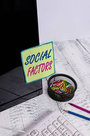 Conceptual hand writing showing Social Factors. Concept meaning Things that influences lifestyle Cultural Differences Note paper taped to black screen near keyboard stationary