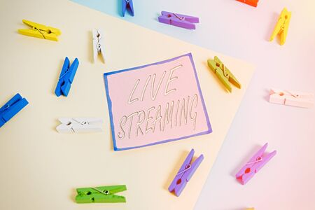 Conceptual hand writing showing Live Streaming. Concept meaning Transmit live video coverage of an event over the Internet Colored clothespin paper reminder with yellow blue background