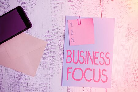 Text sign showing Business Focus. Business photo showcasing Serving the needs of the client Full attention on details Envelope blank sheet paper sticky note smartphone wooden vintage background