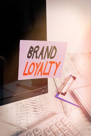 Word writing text Brand Loyalty. Business photo showcasing Repeat Purchase Ambassador Patronage Favorite Trusted Note paper taped to black computer screen near keyboard and stationary