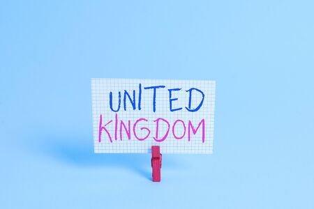 Conceptual hand writing showing United Kingdom. Concept meaning Island country located off the northwestern coast of Europe Colored clothespin rectangle shaped paper blue background Imagens