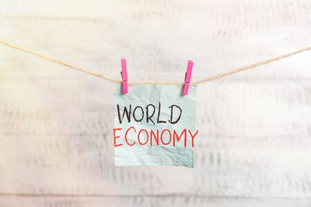 Writing note showing World Economy. Business concept for Global Worldwide International markets trade money exchange Clothesline clothespin rectangle shaped paper reminder white wood desk