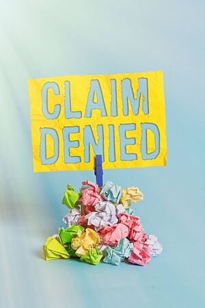 Handwriting text Claim Denied. Conceptual photo Requested reimbursement payment for bill has been refused Reminder pile colored crumpled paper clothespin reminder blue background Imagens