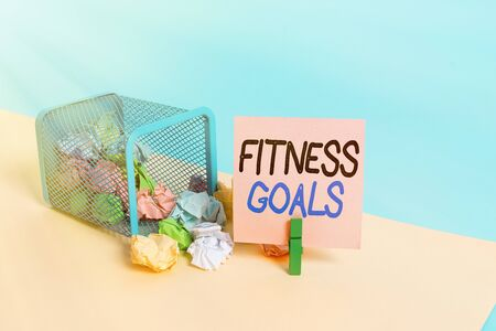 Writing note showing Fitness Goals. Business concept for Loose fat Build muscle Getting stronger Conditioning Trash bin crumpled paper clothespin reminder office supplies
