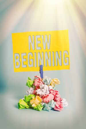 Handwriting text New Beginning. Conceptual photo Different Career or endeavor Starting again Startup Renew Reminder pile colored crumpled paper clothespin reminder blue background