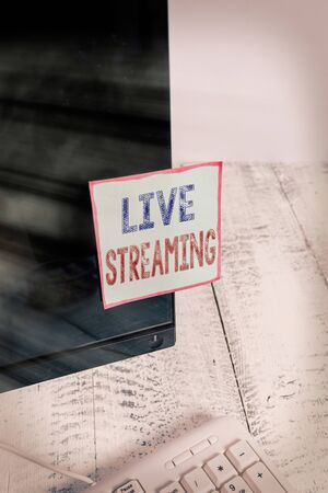 Text sign showing Live Streaming. Business photo showcasing Transmit live video coverage of an event over the Internet Notation paper taped to black computer monitor screen near white keyboard
