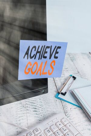 Word writing text Achieve Goals. Business photo showcasing Results oriented Reach Target Effective Planning Succeed Note paper taped to black computer screen near keyboard and stationary 写真素材