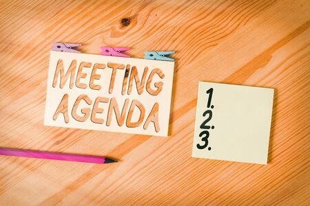 Conceptual hand writing showing Meeting Agenda. Concept meaning An agenda sets clear expectations for what needs to a meeting Colored crumpled papers wooden floor background clothespin