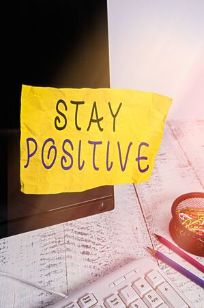 Text sign showing Stay Positive. Business photo showcasing Engage in Uplifting Thoughts Be Optimistic and Real Note paper taped to black computer screen near keyboard and stationary