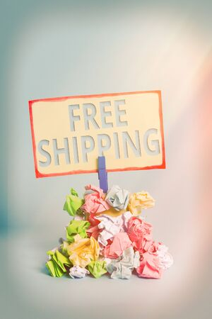 Text sign showing Free Shipping. Business photo text Freight Cargo Consignment Lading Payload Dispatch Cartage Reminder pile colored crumpled paper clothespin reminder blue background