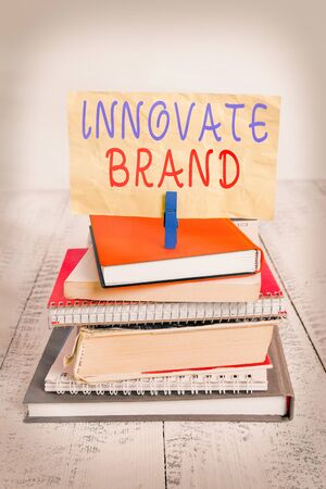 Text sign showing Innovate Brand. Business photo text significant to innovate products, services and more pile stacked books notebook pin clothespin colored reminder white wooden