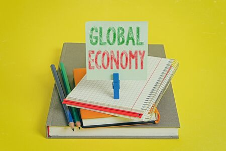 Handwriting text Global Economy. Conceptual photo System of industry and trade around the world Capitalism Book pencil rectangle shaped reminder notebook clothespin office supplies 免版税图像