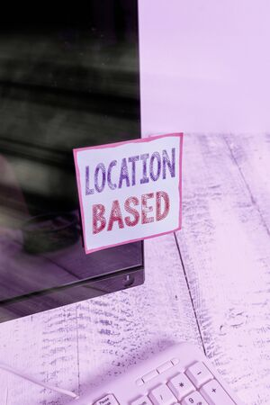 Text sign showing Location Based. Business photo showcasing Mobile marketing to target users within same geographic area Notation paper taped to black computer monitor screen near white keyboard