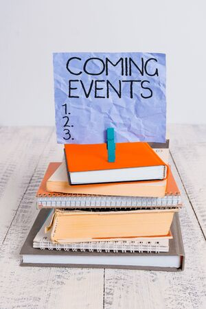 Handwriting text Coming Events. Conceptual photo Happening soon Forthcoming Planned meet Upcoming In the Future pile stacked books notebook pin clothespin colored reminder white wooden