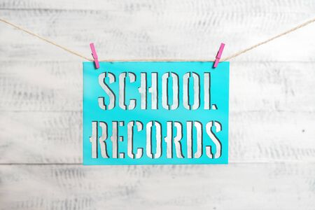 Handwriting text School Records. Conceptual photo Information that is kept about a child at school Biography Clothesline clothespin rectangle shaped paper reminder white wood desk