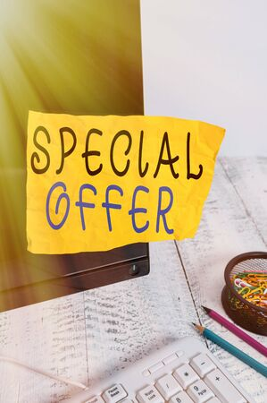 Text sign showing Special Offer. Business photo showcasing Discounted price Markdown Promotional Items Crazy Sale Note paper taped to black computer screen near keyboard and stationary