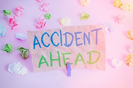 Conceptual hand writing showing Accident Ahead. Concept meaning Unfortunate event Be Prepared Detour Avoid tailgating Colored crumpled papers empty reminder pink floor clothespin