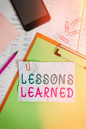 Text sign showing Lessons Learned. Business photo showcasing information reflects positive and negative experiences Clipboard sheet pencil smartphone note clips notepad wooden background