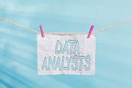 Handwriting text Data Analysts. Conceptual photo Programmer Design and Create Report Identifies patterns Clothesline clothespin rectangle shaped paper reminder white wood desk