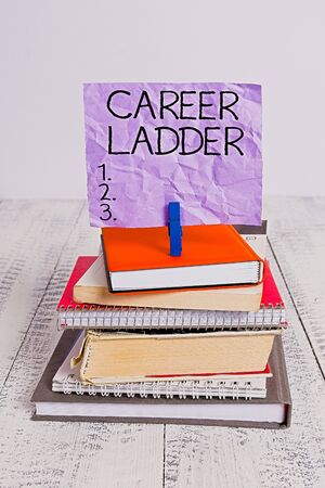 Handwriting text Career Ladder. Conceptual photo Job Promotion Professional Progress Upward Mobility Achiever pile stacked books notebook pin clothespin colored reminder white wooden