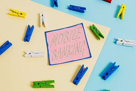 Conceptual hand writing showing Mobile Banking. Concept meaning Monitoring account balances Transferring funds Bill payment Colored clothespin paper reminder with yellow blue background