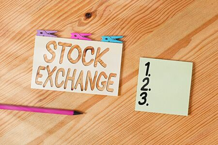 Conceptual hand writing showing Stock Exchange. Concept meaning An electronic market where owners of businesses get together Colored crumpled papers wooden floor background clothespin