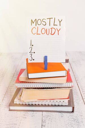 Word writing text Mostly Cloudy. Business photo showcasing Shadowy Vaporous Foggy Fluffy Nebulous Clouds Skyscape pile stacked books notebook pin clothespin colored reminder white wooden