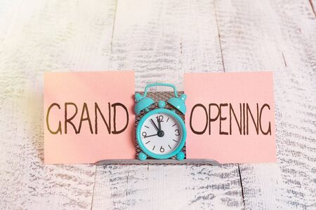 Writing note showing Grand Opening. Business concept for Ribbon Cutting New Business First Official Day Launching Mini blue alarm clock standing above buffer wire between two paper
