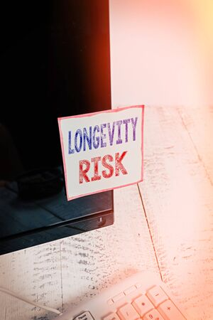 Text sign showing Longevity Risk. Business photo showcasing Potential threat due to increasing lifespan of pensioners Notation paper taped to black computer monitor screen near white keyboard