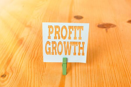Handwriting text Profit Growth. Conceptual photo Objectives Interrelation of Overall Sales Market Shares Empty reminder wooden floor background green clothespin groove slot office