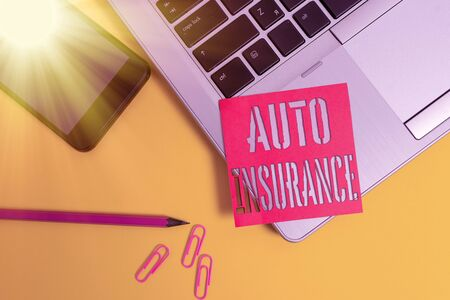 Text sign showing Auto Insurance. Business photo showcasing Protection against financial loss in case of accident Trendy laptop smartphone blank sticky note pencil clips colored background Zdjęcie Seryjne