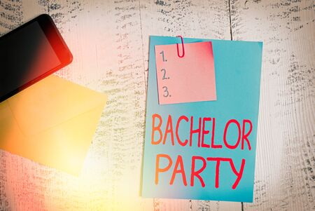Text sign showing Bachelor Party. Business photo showcasing Party given for a man who is about to get married Stag night Envelope blank sheet paper sticky note smartphone wooden vintage background