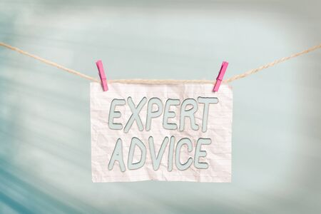 Handwriting text Expert Advice. Conceptual photo Sage Good Word Professional opinion Extensive skill Ace Clothesline clothespin rectangle shaped paper reminder white wood desk Banco de Imagens