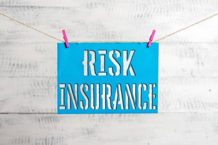 Handwriting text Risk Insurance. Conceptual photo The possibility of Loss Damage against the liability coverage Clothesline clothespin rectangle shaped paper reminder white wood desk Zdjęcie Seryjne