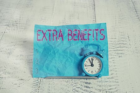Text sign showing Extra Benefits. Business photo showcasing Additional compensation Bonus Subsidies Incentives Allowances Mini blue alarm clock stand tilted above buffer wire in front of notepaper