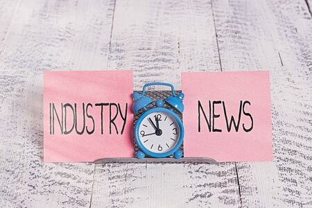 Writing note showing Industry News. Business concept for Technical Market Report Manufacturing Trade Builder Mini blue alarm clock standing above buffer wire between two paper Foto de archivo