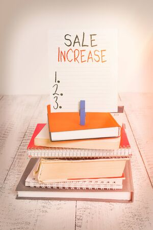 Word writing text Sale Increase. Business photo showcasing Average Sales Volume has Grown Boost Income from Leads pile stacked books notebook pin clothespin colored reminder white wooden Banco de Imagens