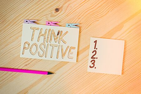 Conceptual hand writing showing Think Positive. Concept meaning The tendency to be positive or optimistic in attitude Colored crumpled papers wooden floor background clothespin