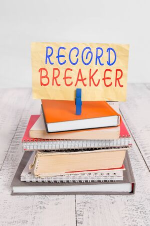 Text sign showing Record Breaker. Business photo text someone or something that beats previous best result pile stacked books notebook pin clothespin colored reminder white wooden Stock Photo