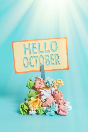 Text sign showing Hello October. Business photo text Last Quarter Tenth Month 30days Season Greeting Reminder pile colored crumpled paper clothespin reminder blue background