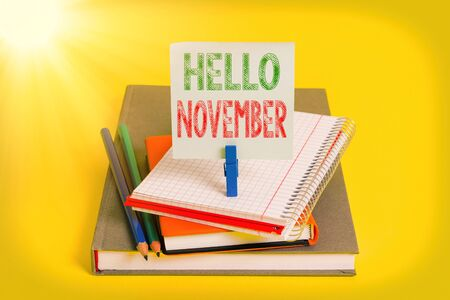 Handwriting text Hello November. Conceptual photo Welcome the eleventh month of the year Month before December Book pencil rectangle shaped reminder notebook clothespin office supplies