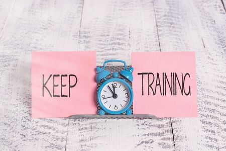 Writing note showing Keep Training. Business concept for Grounding Drilling Always Wonder Be Curious Learn Mini blue alarm clock standing above buffer wire between two paper Фото со стока