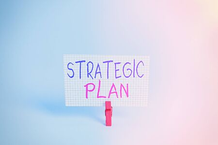 Conceptual hand writing showing Strategic Plan. Concept meaning A process of defining strategy and making decisions Colored clothespin rectangle shaped paper blue background Stockfoto