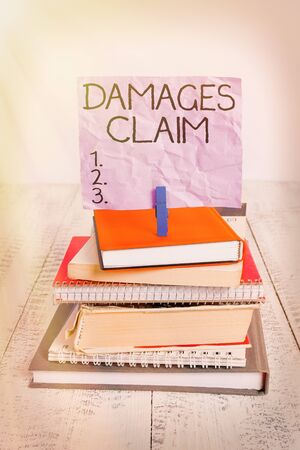 Handwriting text Damages Claim. Conceptual photo Demand Compensation Litigate Insurance File Suit pile stacked books notebook pin clothespin colored reminder white wooden