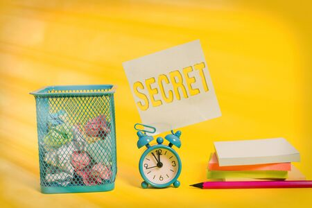 Writing note showing Secret. Business concept for something that is kept or meant to be kept unknown to others Alarm clock pencil note paper balls container pads colored background