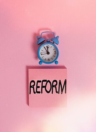 Handwriting text writing Reform. Conceptual photo to amend or improve by change of forms or removal of faults Vintage alarm clock wakeup blank notepad sticky note colored background