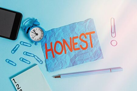 Conceptual hand writing showing Honest. Concept meaning telling the truth or able to be trusted and not likely to steal Alarm clock notepad smartphone band marker colored background