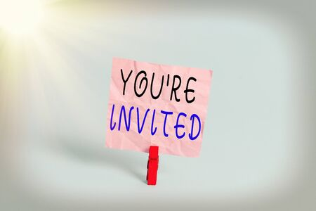 Writing note showing You Re Invited. Business concept for make a polite friendly request to someone go somewhere Colored clothespin rectangle square shaped paper light blue background